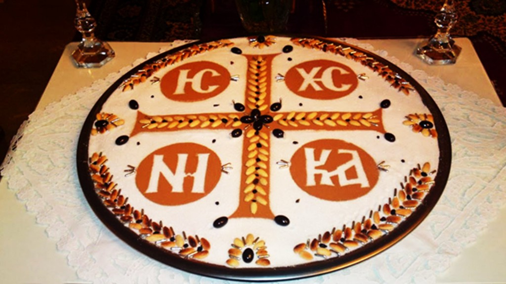 A photo of kolyva with an ornate cross on top, placed on a table